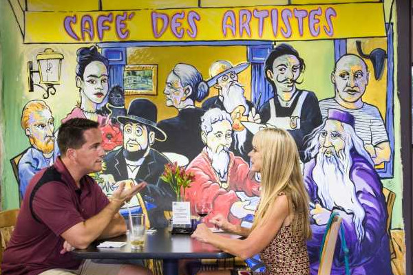 Patrons enjoying coffee in our cafe with artistic backdrops